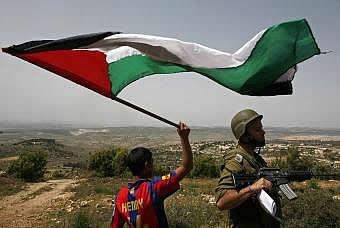 Un niño ondea una bandera palestina ante un militar israelí