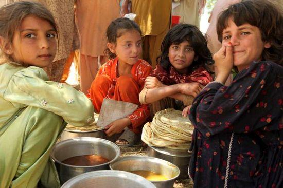 Niñas reciben alimentos en Pakistán. Copyright: UNHCR/H. Caux
