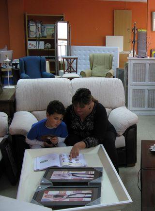 Un madre ayuda a su hijo con los deberes en la tienda que regenta - Foto: Francisco Bonilla