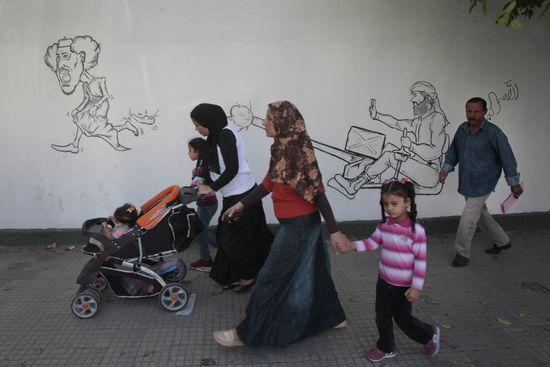 Un grupo de personas camina ante una caricatura de Gadafi en Trípoli. / CRISTÓBAL MANUELLibia