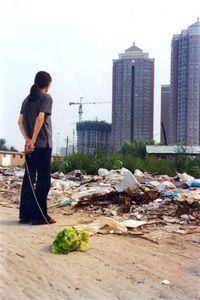 El artista chino Han Bing pasea un repollo frente a New City, en Wangjing (Pekín), en 2001 (Estudio Han Bing)