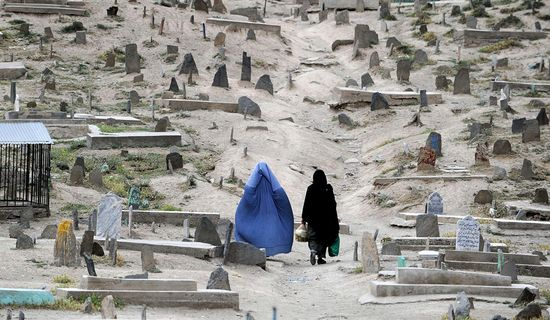 Dos mujeres caminan por un cementerio de Kabul. / PUNIT PARANJPE (AFP)