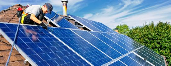 Un operario instala unas placas fotovoltaicas_iStockphoto