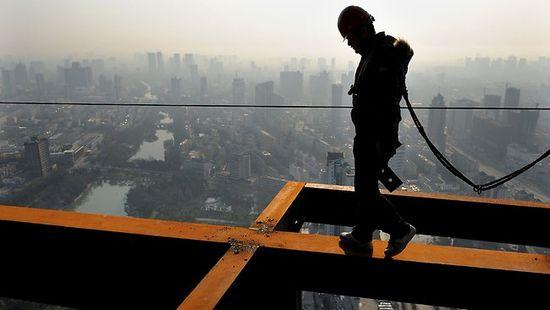 Un trabajdor camina sobre una viga en una obra en Hefei, capital de la provincia de Anhui. (AFP)