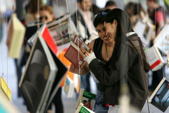 """Una pareja de mujeres hojea un libro que forma parte de la instalación """"La noche de los libros"""" en la calle de Fuencarral (Madrid) con motivo del Día del Libro. © ULY MARTÍN"""