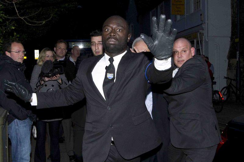 Guardas de seguridad protegen a DSK, oculto en el centro de la imagen. / CARL COURT (AFP)