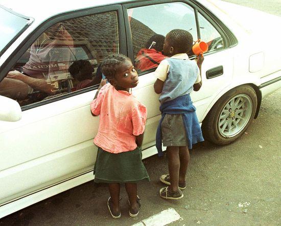 Dos niñas huérfanas a causa del sida piden limosna en Harare (Zimbabue). / AP