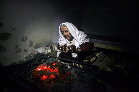 Una mujer se calentaba junto al fuego el mes pasado en los restos de una casa destruida tras una ofensiva israelí en la Franja de Gaza. ALI ALI (EFE)