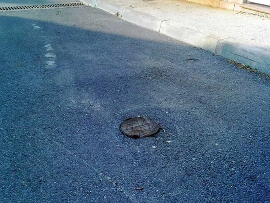 Observar el palo de la luz cortado a ras del asfalto