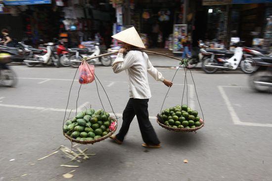 Una mujer, vendedora ambulante, con su mercancía en dos cestos que cuelgan de una barra en los que lleva fruta, en una calle de Hanoi (Vietnam). Uly Martin