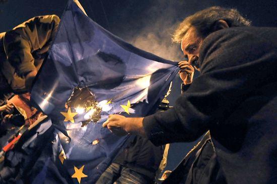 Varios manifestantes griegos queman una bandera de la UE en Atenas / Foto: France Press