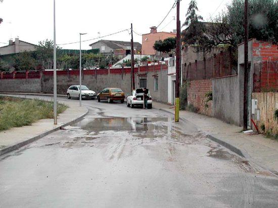 Calle Can Bosch asfaltado y el agua estancada