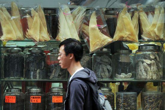 Un hombre pasa delante de un comercio en el que se venden aletas de tiburón en Hong Kong. (AFP)
