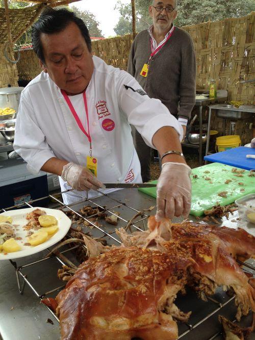 Juan Talledo, el gestor de la caja china en Mistura troceando un cerdo recién asado, bajo la mirada del periodista español Ignacio Medina