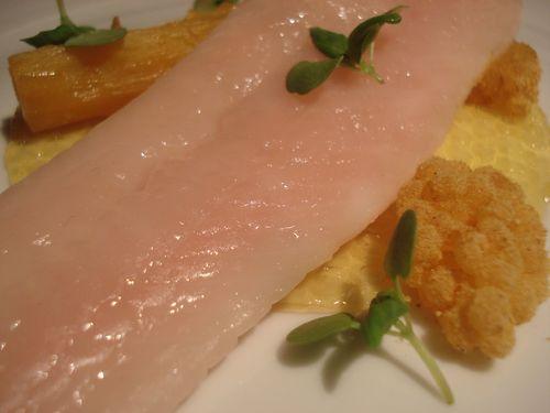 Pescado cocinado bajo capa de cera ya en el plato con su guarnición