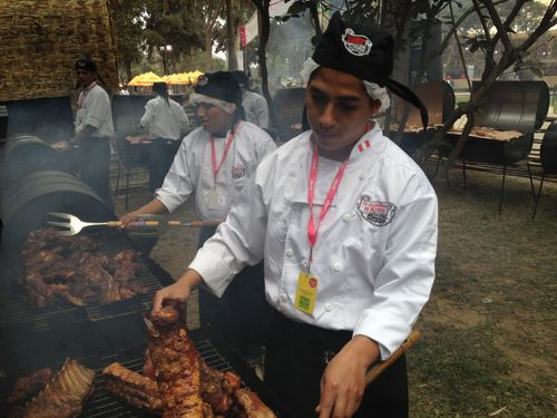 Cocineros peruanos poniendo a punto los asados en cilindro horizontal