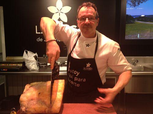 Carnicero a punto de cortar un chuletón en el puesto que la familia Jiménez Barbero tiene en el mercado de San Antón, en Madrid