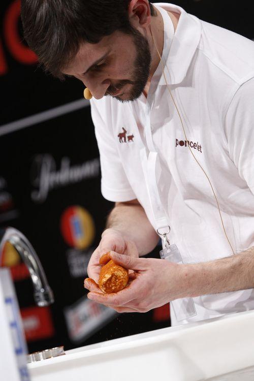 Embadurnando un queso de cabra con forma de rulo con pimentón
