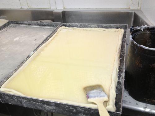 Base del hojaldre. Masa de harina, sal y agua extendida sobre una plancha que descansa en una base fría, una cubeta repleta de cubitos de hielo. Con la brocha se extiende la manteca de cerdo licuada