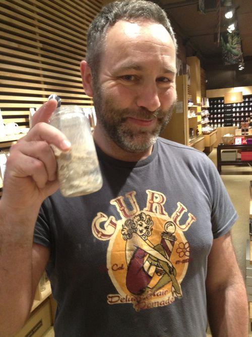 El periodista y panadero Javier Marca en la tienda de Cacao Sampaka en Madrid. En la mano un tarrito de masa madre que utiliza para elaborar los panes que a diario vende en ese comercio con un éxito desmesurado