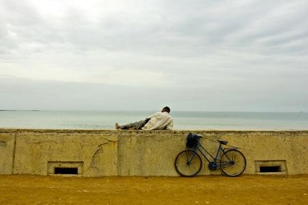 Un hombre con su bici junto a una de las playas de Casablanca.