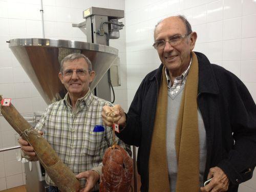 Tomeu Frau, propietario de La Luna y Mateo Castelló, presidente del Consejo Regulador de la IGP Sobrasada de Mallorca, sosteniendo dos grandes piezas de sobrasada