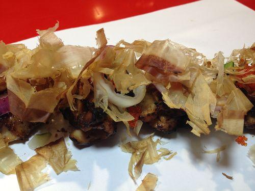 Espeto de pollo pekinés con bonito ahumado (katsuobushi). Huevas de pez volador (tobiko), yogur, 5 especias chinas, cebolla encurtida. El pollo se cocina a baja temperatura y se asa en horno de carbón. Finalmente se saltea en el wok para lograr el sabor de la combustión. Espléndido