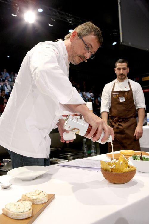 Andoni Aduriz vertiendo crema de queso sobre un cuenco de nachos
