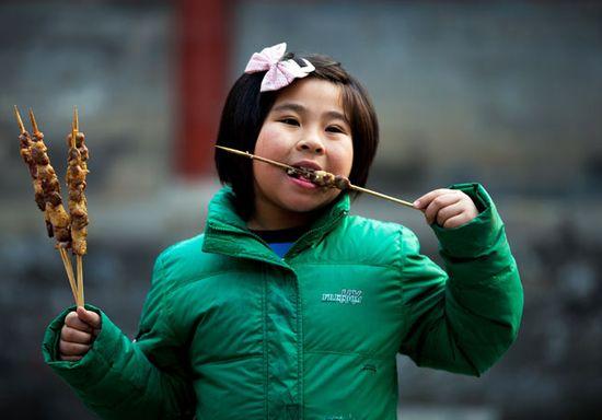 Una niña come brochetas de cordero en una feria en el templo Dongyue, en Pekín. (AP)