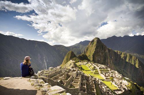 Una turista contemplando la ciudad inca de Machu Picchu, en Perú. / CORBIS