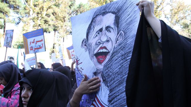 File photo shows an Iranian woman holding a cartoon of US President Barack Obama during a rally outside the former US Embassy in Tehran. November 2, 2012.