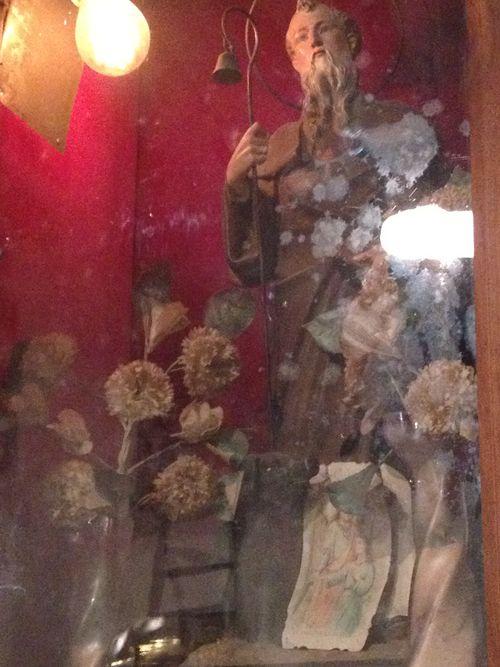 Imagen de San Antonio situada en el museo de la primitiva fábrica. A los pies del santo se ve malamente un cerdo negro que parece un perro