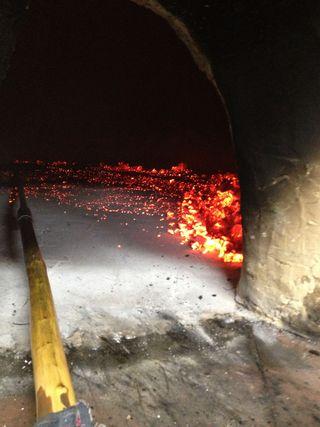 Uno de los hornos de asar de Manix contemplado desde la boca con brasas de madera de encina