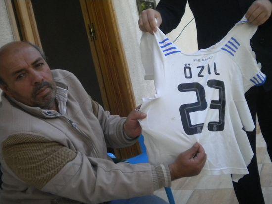 El padre de Ahmed Abu Daqqa muestra la camiseta que llevaba su hijo cuando fue asesinado / M. Á. Medina
