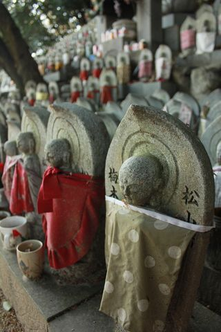 Estatuillas protegidas con baberos en el templo de Ishiteji