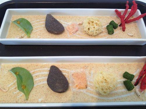 Bandejas del denominado Jardin Marino que Subijana y su equipo elaboran a la vista de los clientes desvelando los secretos de cada pieza. En el fondo de cada plato arenas de gambas, y de izquierda a derecha, hoja de ostra, mejillón con su cáscara (comestible), esponja de erizos, piedras de playa (chalotas y maíz) y coral de alga codium (tempura con sabor a percebe)