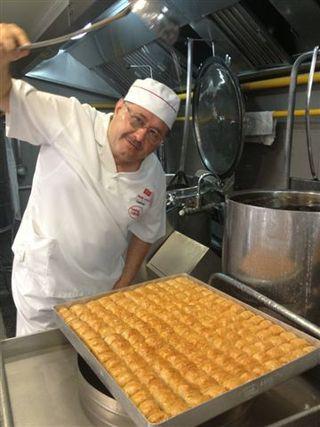 El pastelero Nadir Güllü vertiendo almíbar sobre las bandejas de backlavas al salir del horno
