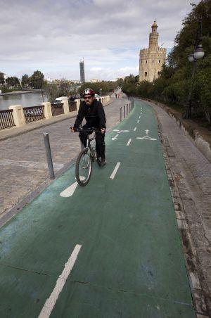 Un hombre pedaleando en el carril bici de Sevilla con la Torre del Oro a su espalda. Foto de Julián Rojas