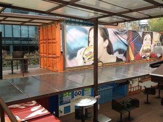 Estructura montada con contenedores superpuestos que dan lugar a una espacio comercial repleto de restaurantes y pastelerías que se alojan en el espacio de un contenedor