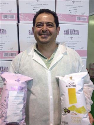 Rafael del Rosal mostrando dos bolsas de sus famosas patatas. En la mano izquierda la destinada al mercado americano