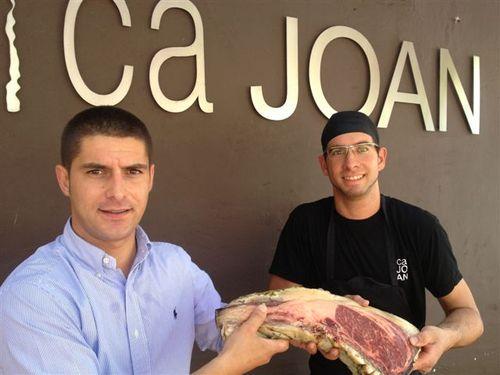 Joan Abril y su maestro asador mostrando un chuletón de buey de larga maduración