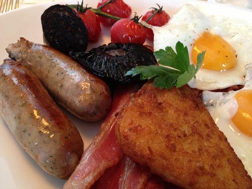 Desayuno inglés en el Me London de Melià. Salchichas, morcilla y beicon. Setas y tomates salteados, huevos y patatas aplastadas y doradas en la sartén.