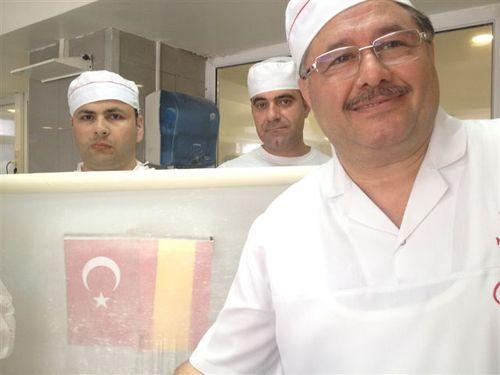 """Para demostrar la finura de sus masas estiradas, el pastelero turco Nadir Güllü, con la ayuda de dos operarios, colocó las banderas turca y española detrás de una de estas """"gasas"""" enrolladas.Tan finas como para poder leer un periódico"""