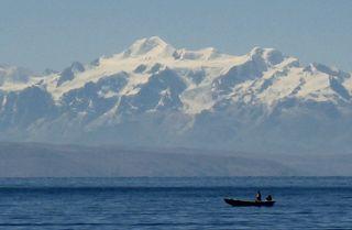 Una barca cruza el lago Titicaca con los Andes al fondo