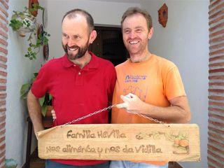 Los hermanos Hevilla bromeando con un cartel que llevan a las ferias locales en las que venden sus productos. A la izquierda Sebastián, gerente de Guadalhorce Ecológico