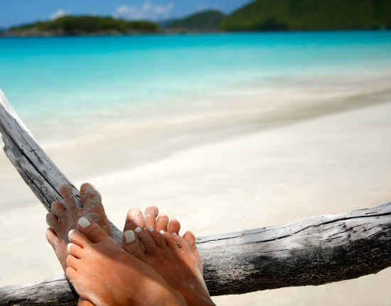 Couples-feet-on-perfect-tropical-beach-resting-on-driftwood