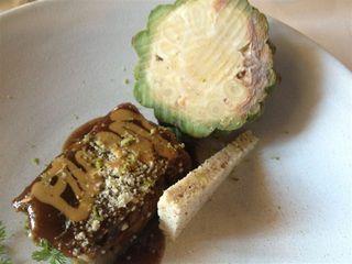 Terrina de morros de ternera empiñonada sobre la que se ralla piña verde, en un costado del plato congelada