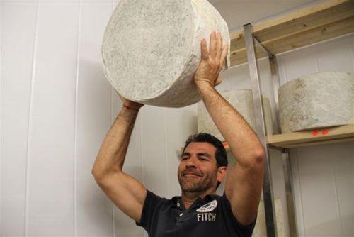 Paco Roncero,herculéo  sosteniendo un queso tipo chedar