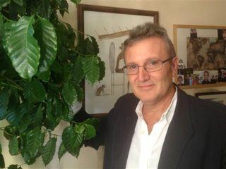 Ricardo Oteros en su despacho, mostrando una planta del café que le produce frutos