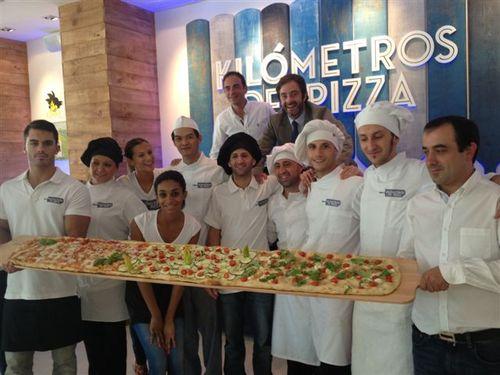 Parte del equipo de Kilómetros de Pizza, sujetando una pieza de 2 metros